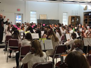 Students holding string instruments sit in chairs watching conductor