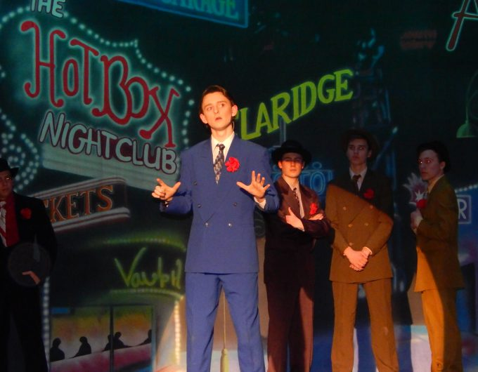 Boy in blue suit sings in character on stage