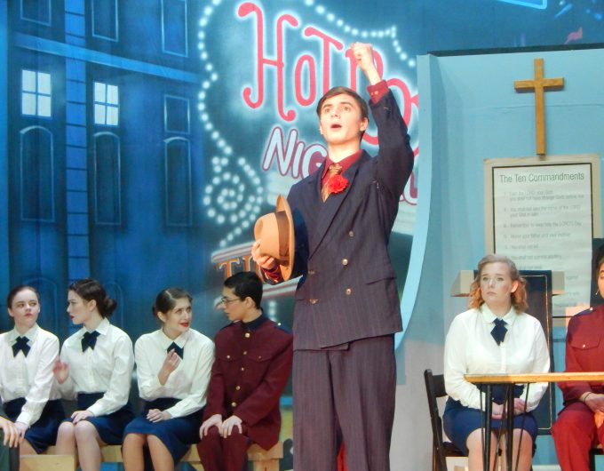 Boy in dark suit sings on stage while several students sit in background