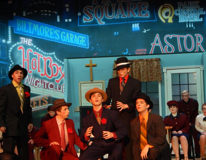 Group of boys dressed in suits perform on stage