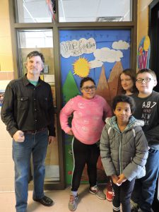 man stands with four students in front of colorfully decorated classroom door