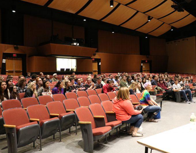 Students sit in auditorium seats