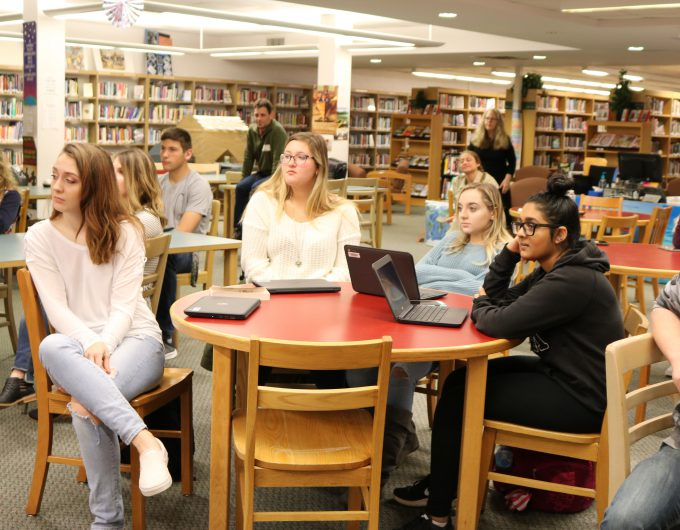 Students sit at round tables in library