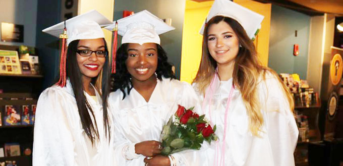 3 high school female graduates pose in their caps and gowns, one holding roses