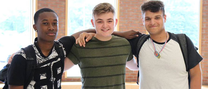 3 male high school students with arms around one another