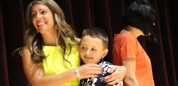 teacher hugs young boy at graduation