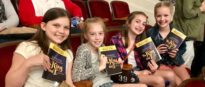 4 girls holding their play programs and smiling
