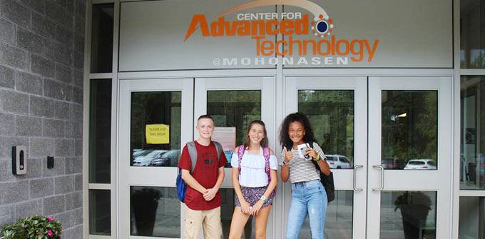 3 students stand in the doorway of the CAT center