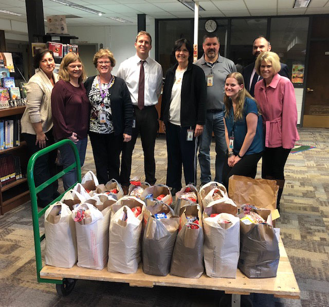 Nine people stand behind cart containing grocery bags filled with food