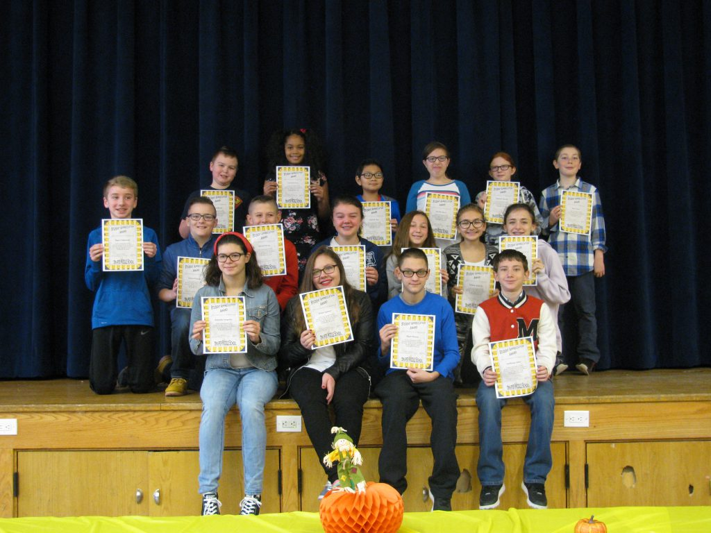 group of students hold up their award certificates