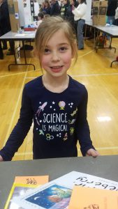 Student smiles at table wearing a shirt that says SCIENCE IS MAGICAL