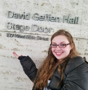 Student poses in front of engraved sign that says David Getton Hall Stage Door.