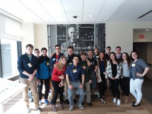 About 20 students stand in front of a black and white mural at GE