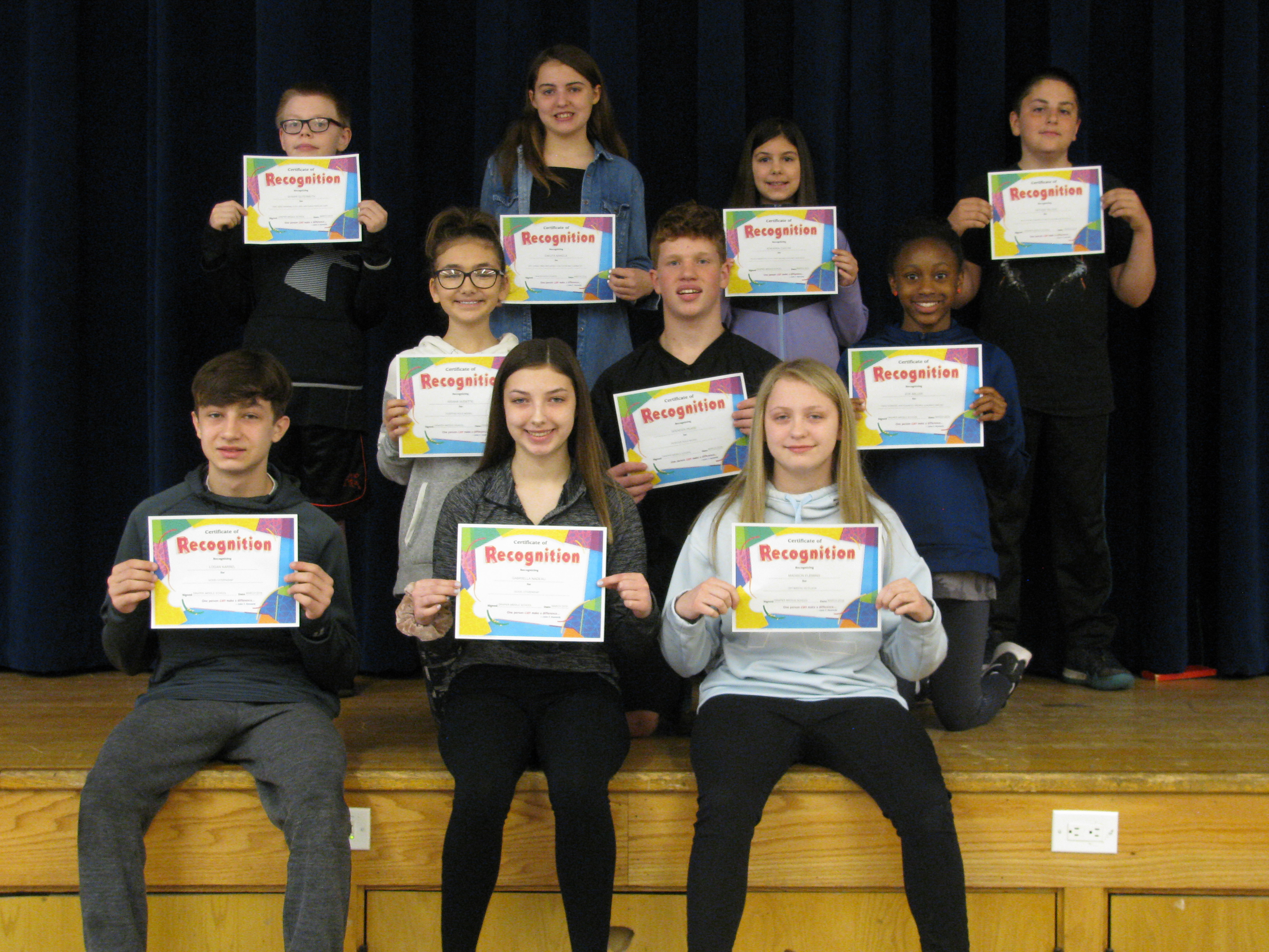 students hold their award certificates