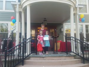 Ronald McDonald House, students stand on steps surrounded by balloons.