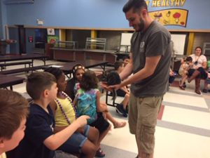 Students pet a chinchilla during a visit from the zoo.
