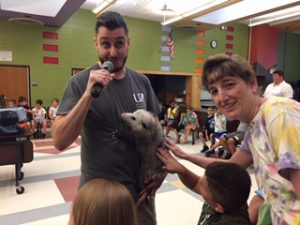 Students visit a possum during a visit from the zoo.