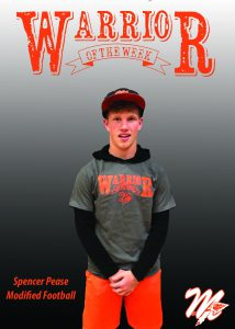 Student wears a tshirt that reads WARRIOR. Warrior of the Week is displayed above him.