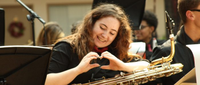 student makes a heart shape with hands while playing an instrument
