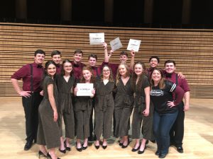 group of a capella students with award