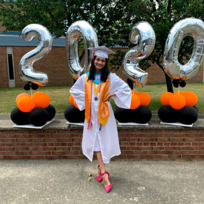 photo of Sophia Sacchetti smiling in front of orange and black balloons and 2020 balloons