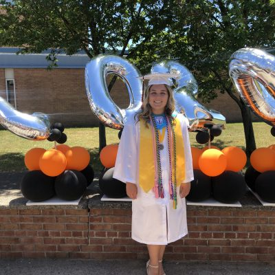 photo of Julianna Huba in front of orange and black balloons and 2020 balloons