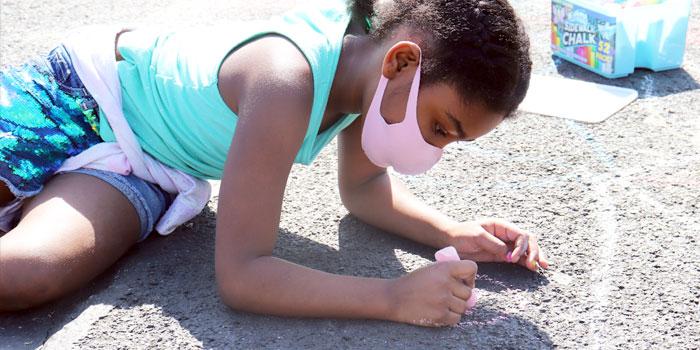 student using sidewalk chalk on a sunny day