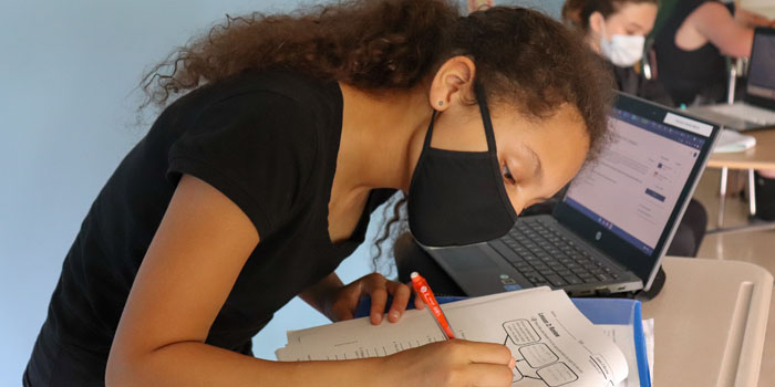close-up of student filling writing with a pencil on classroom assignment