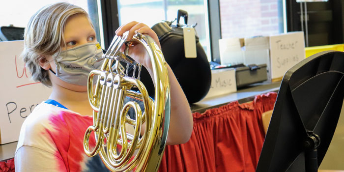 student plays French horn in music class
